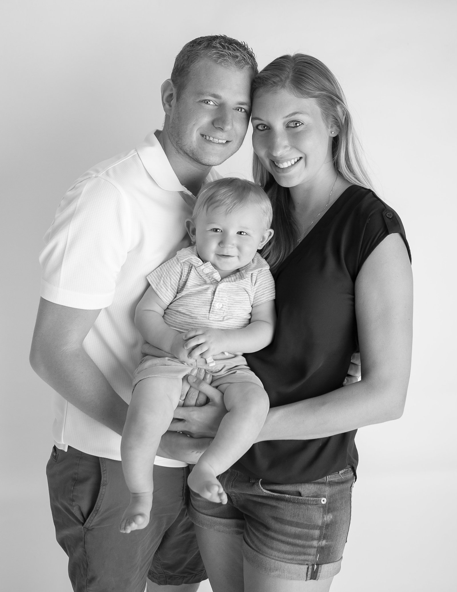 Black/white image - Mom, dad and one year old son, standing and smiling - In studio