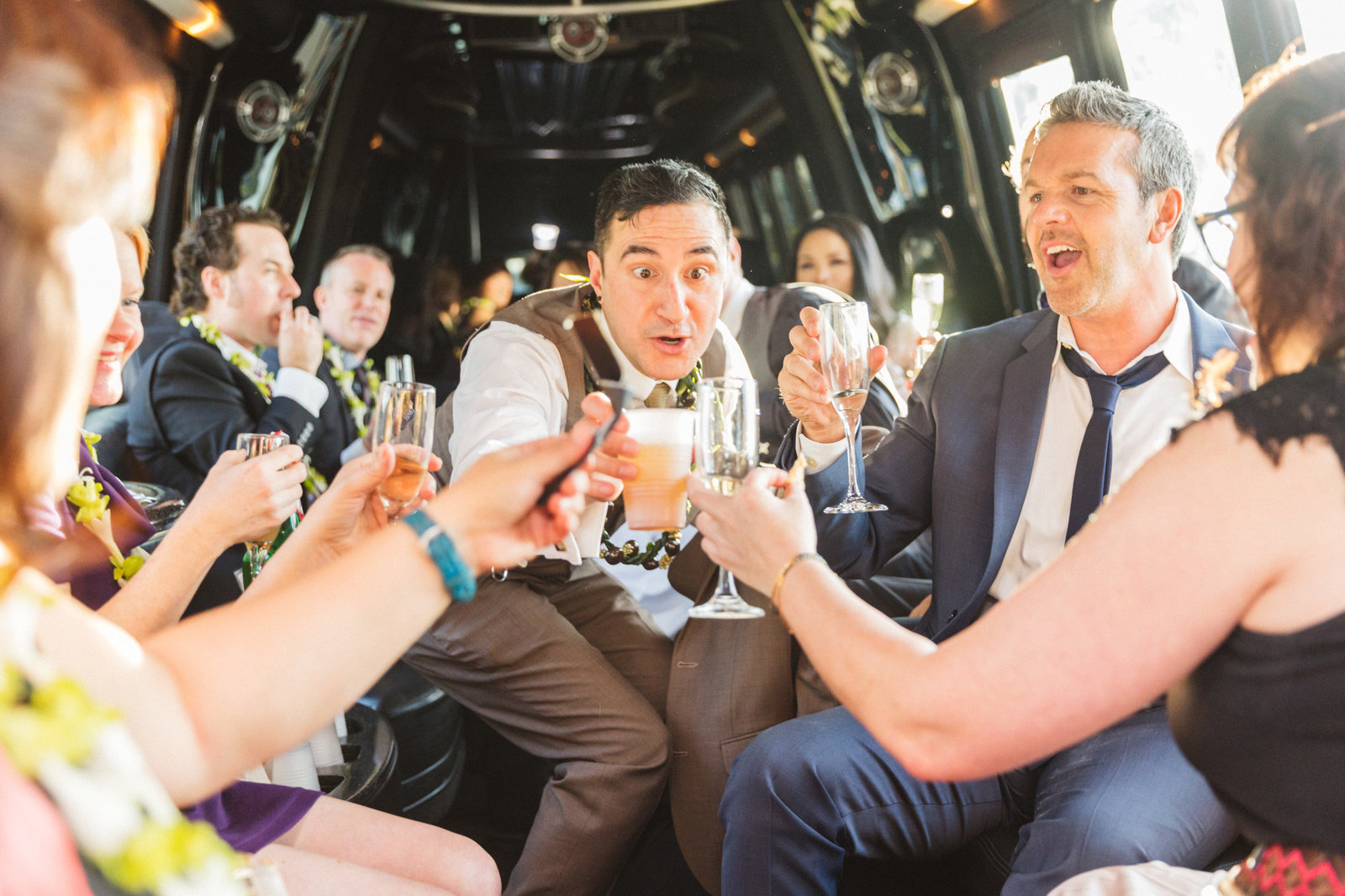 groom in back of limo toasting champagne with guest