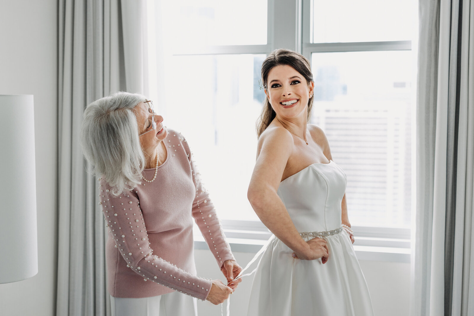 mom helping bride into wedding dress