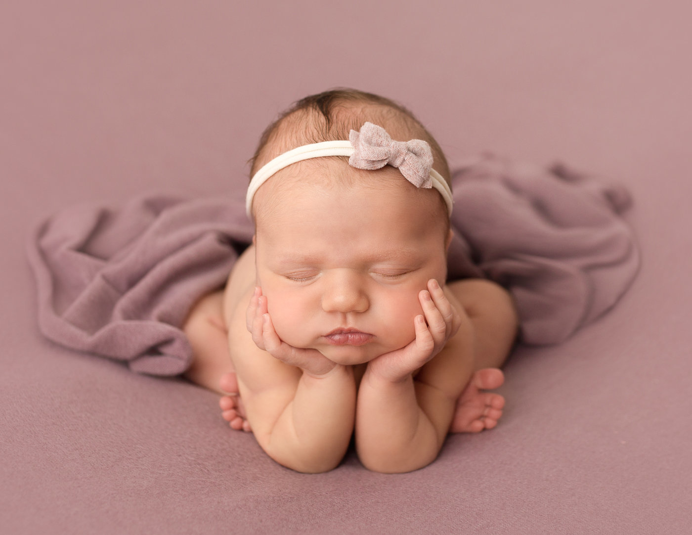 Sweet newborn girl in froggy pose in our Rochester, NY studio.