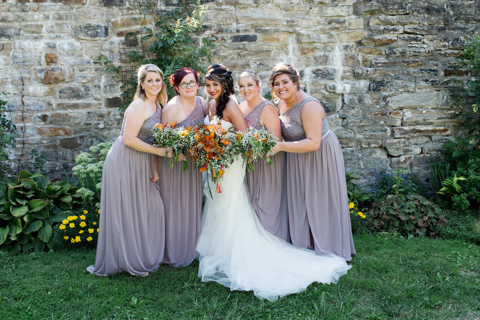 bride stands with her bridesmaids in front of a stone wall