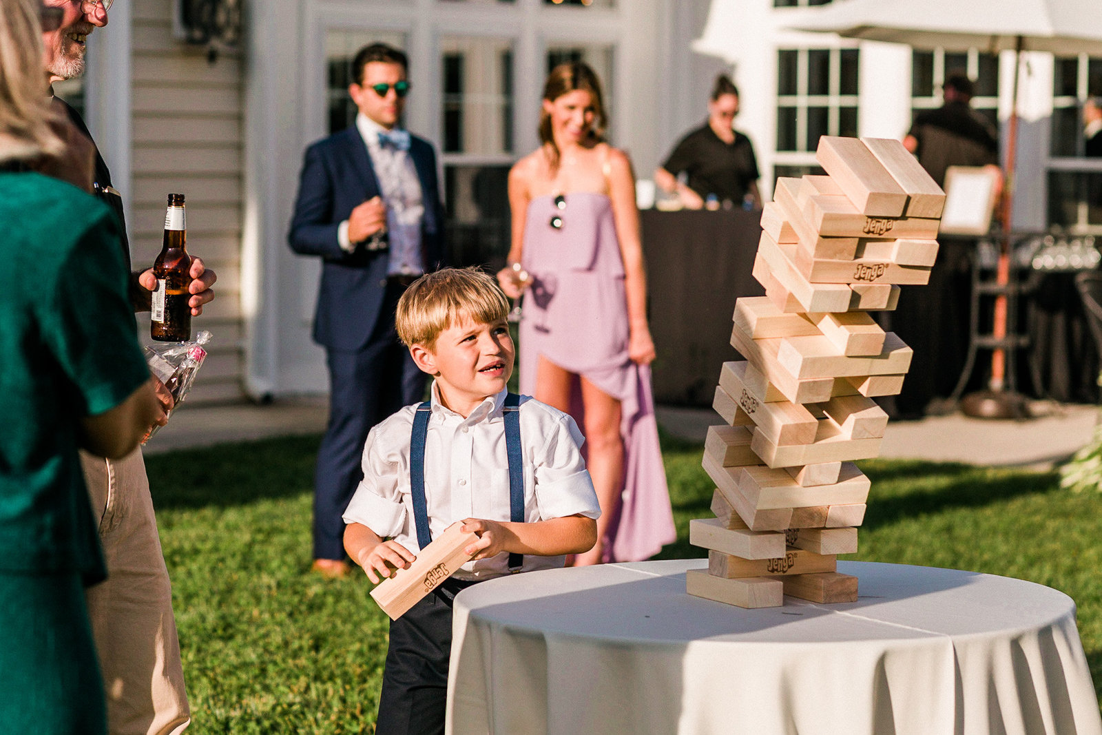 Child watches as a jenga tower collapses at a wedding