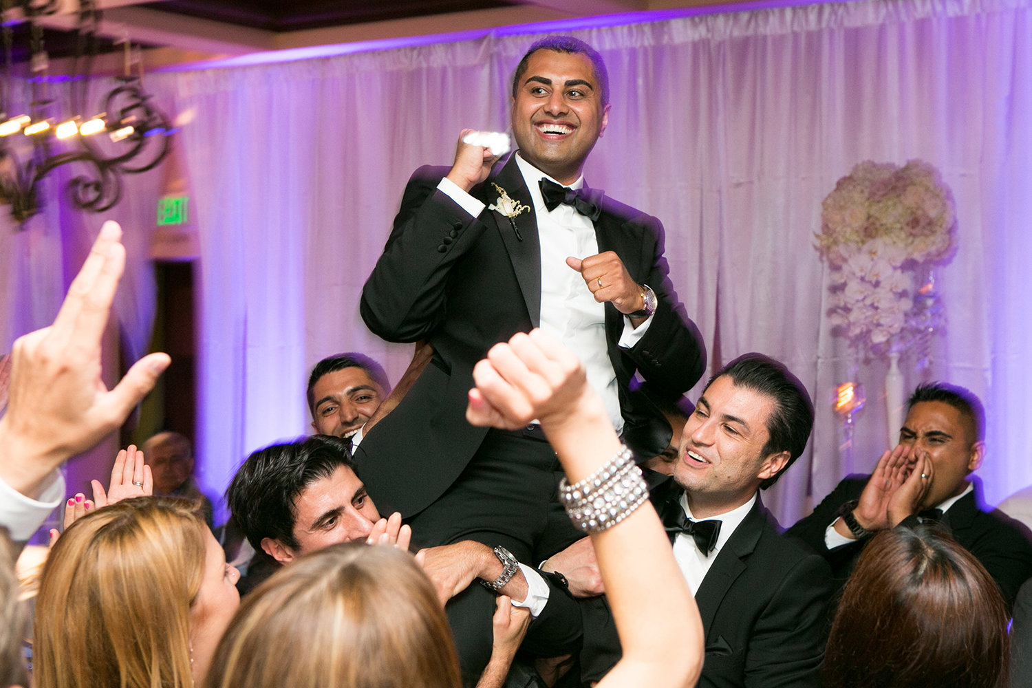 Groom hoisted up in the air during the reception