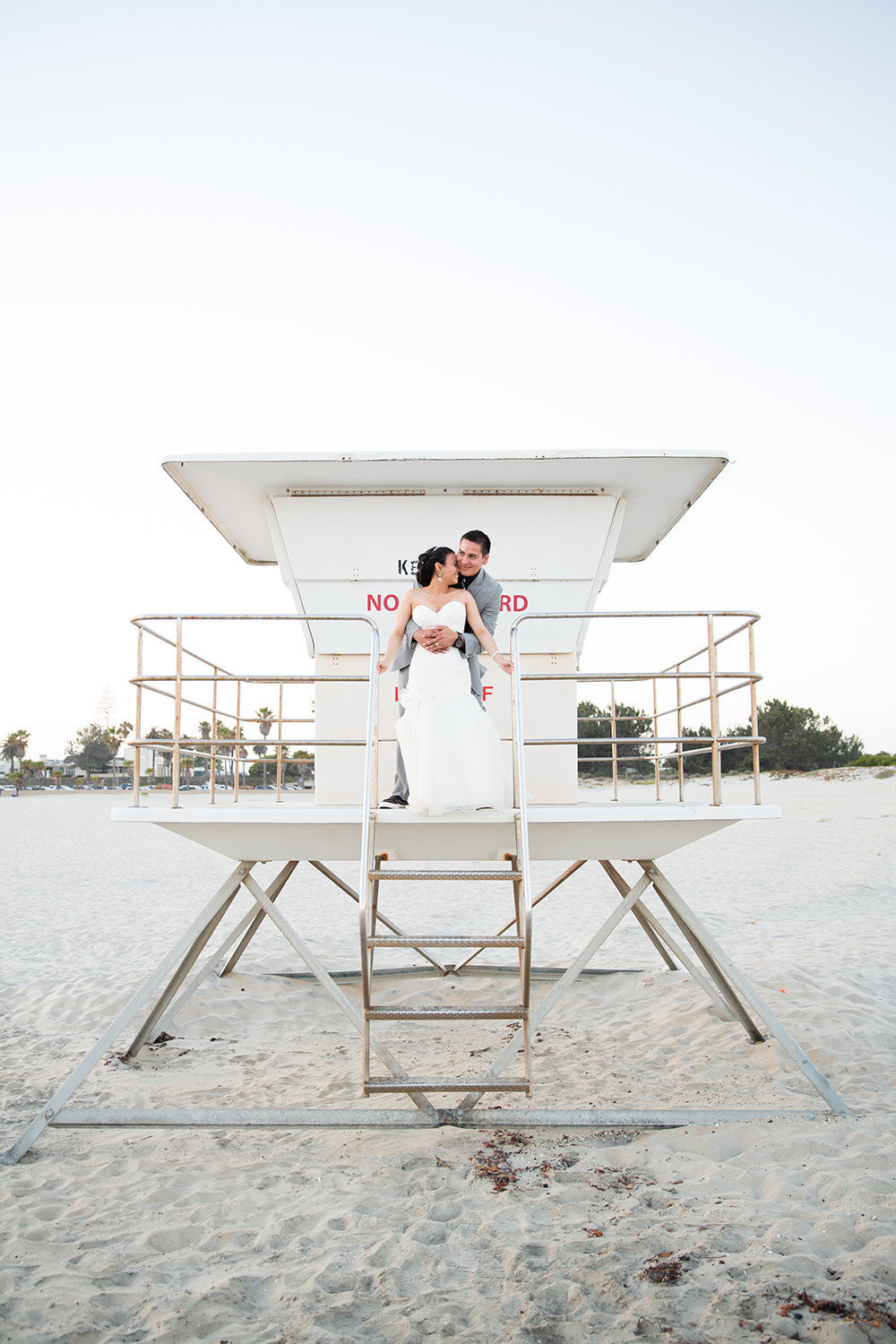 bride and groom on life guard tower at ocean view room