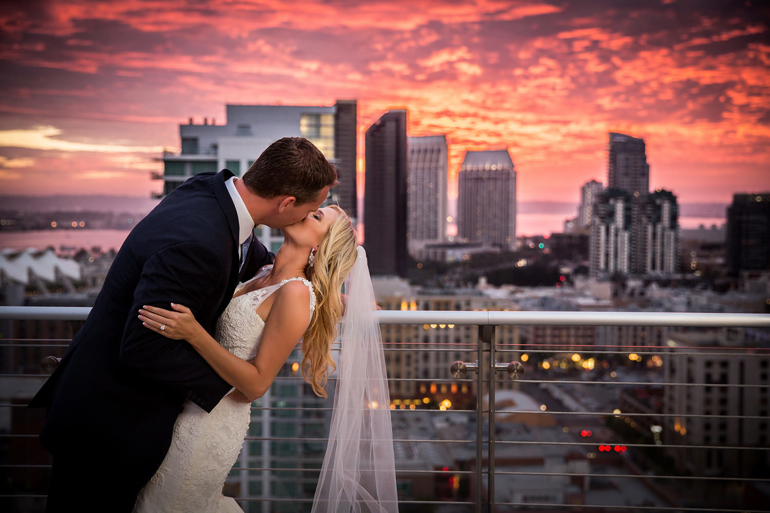 Bride and groom kiss with a surreal sunset over downtown San Diego