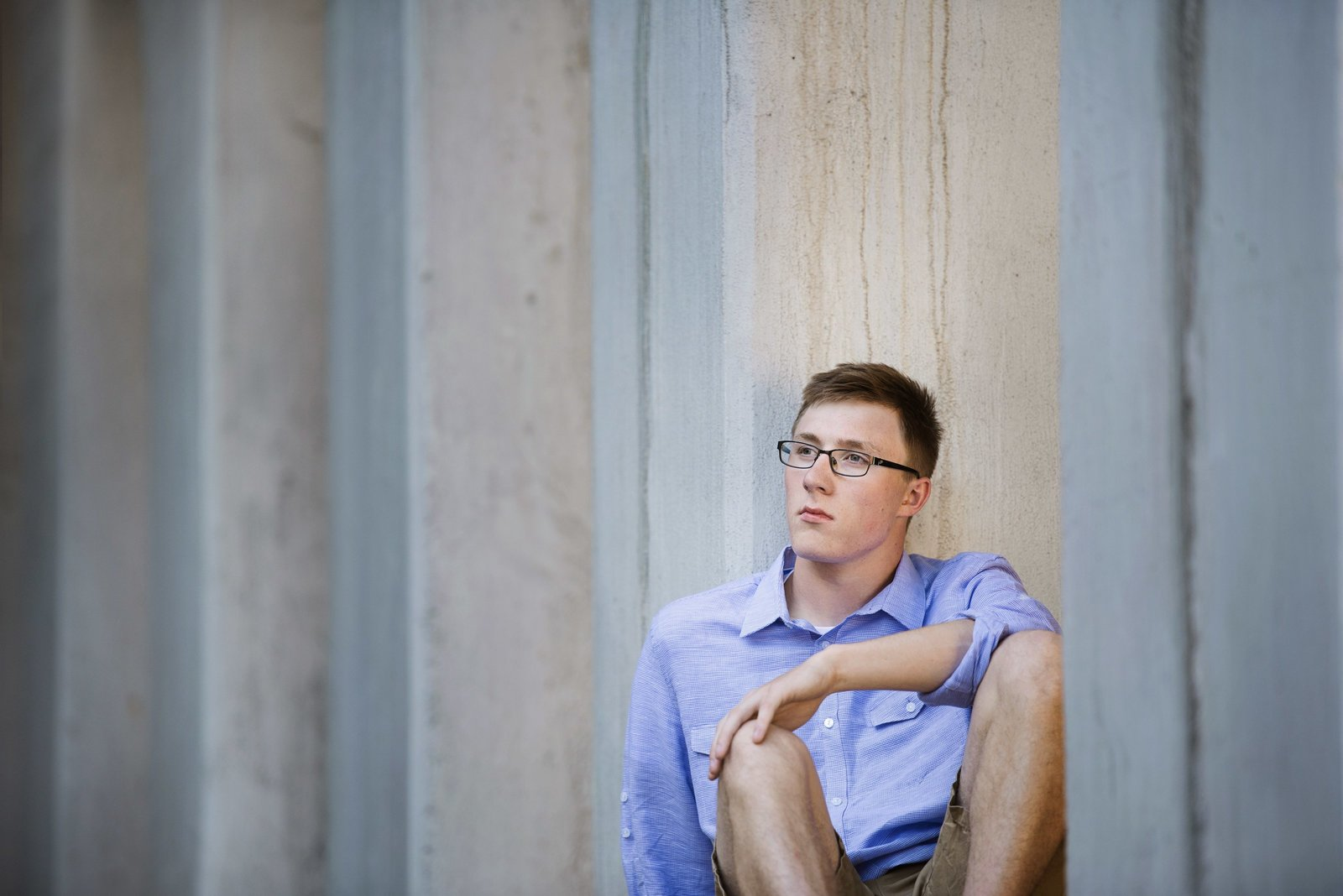 Senior picture of boy sitting against wall