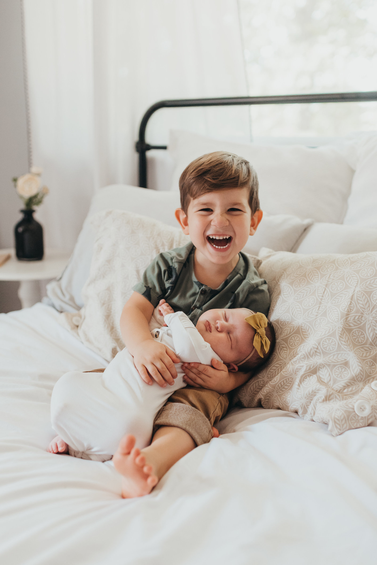 brother holding baby sister on a bed