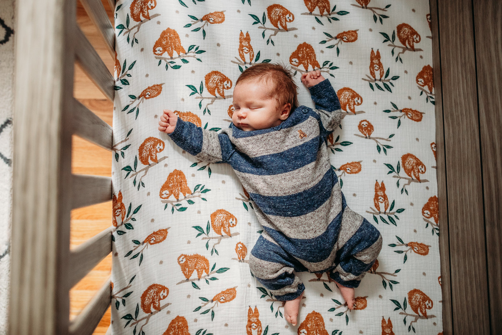 baby boy in striped outfit lies on sloth sheets in crib during newborn pictures in sherborn ma