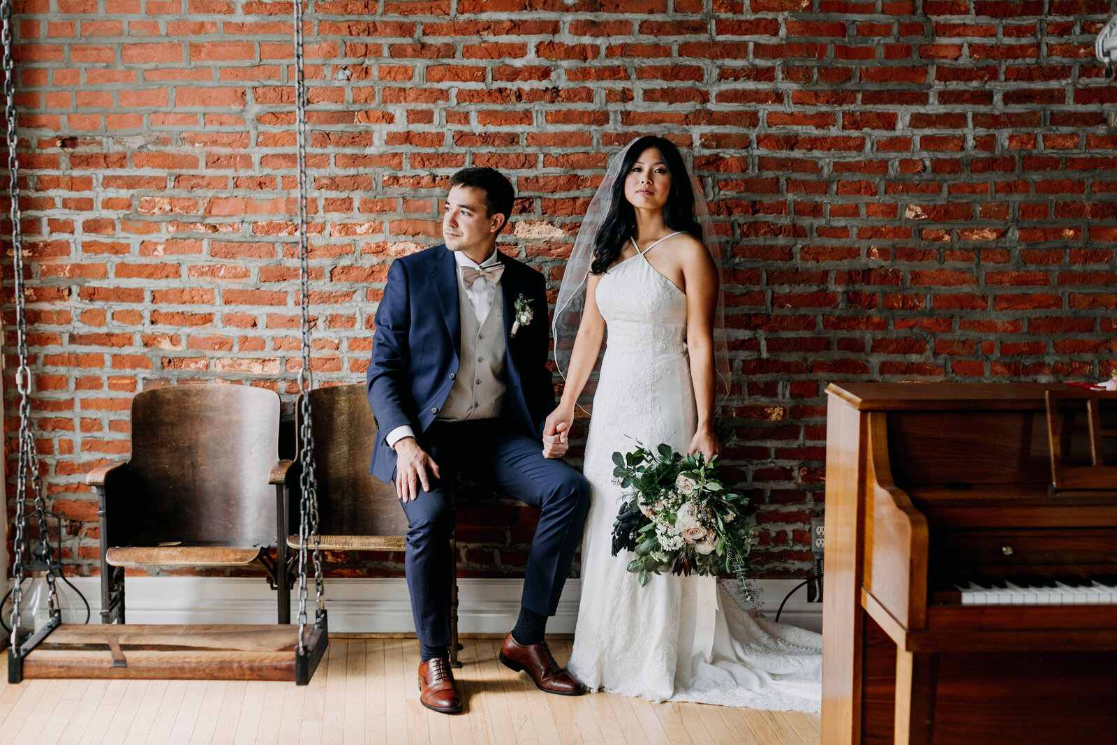 bride and groom with brick wall and piano