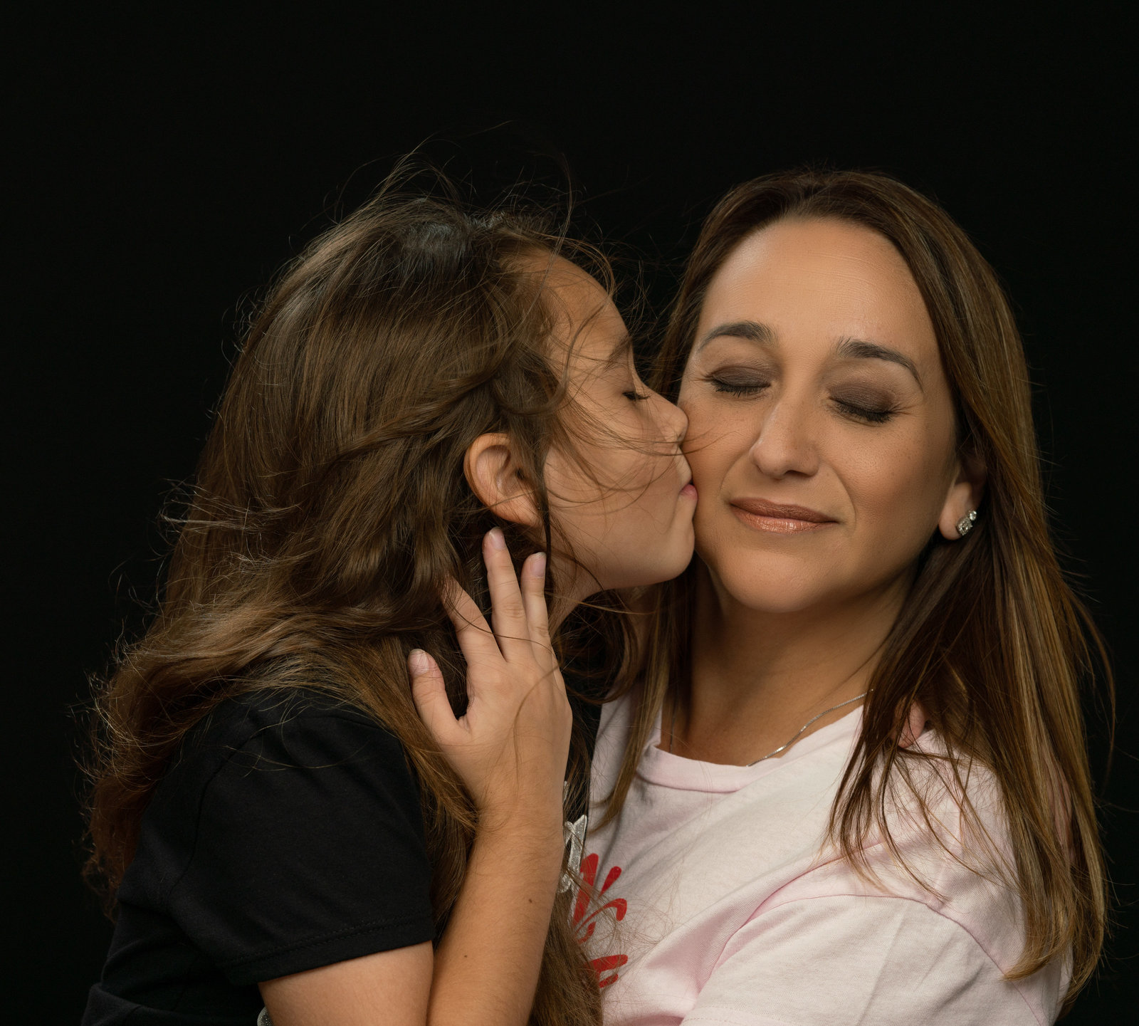 Daughter kissing mother with eys closed