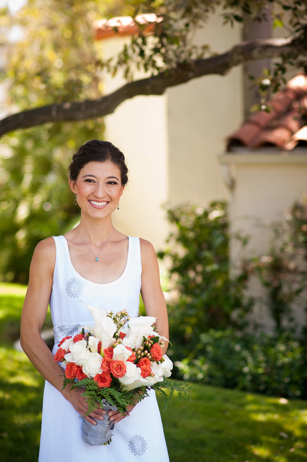 bride with white and orange bouquet