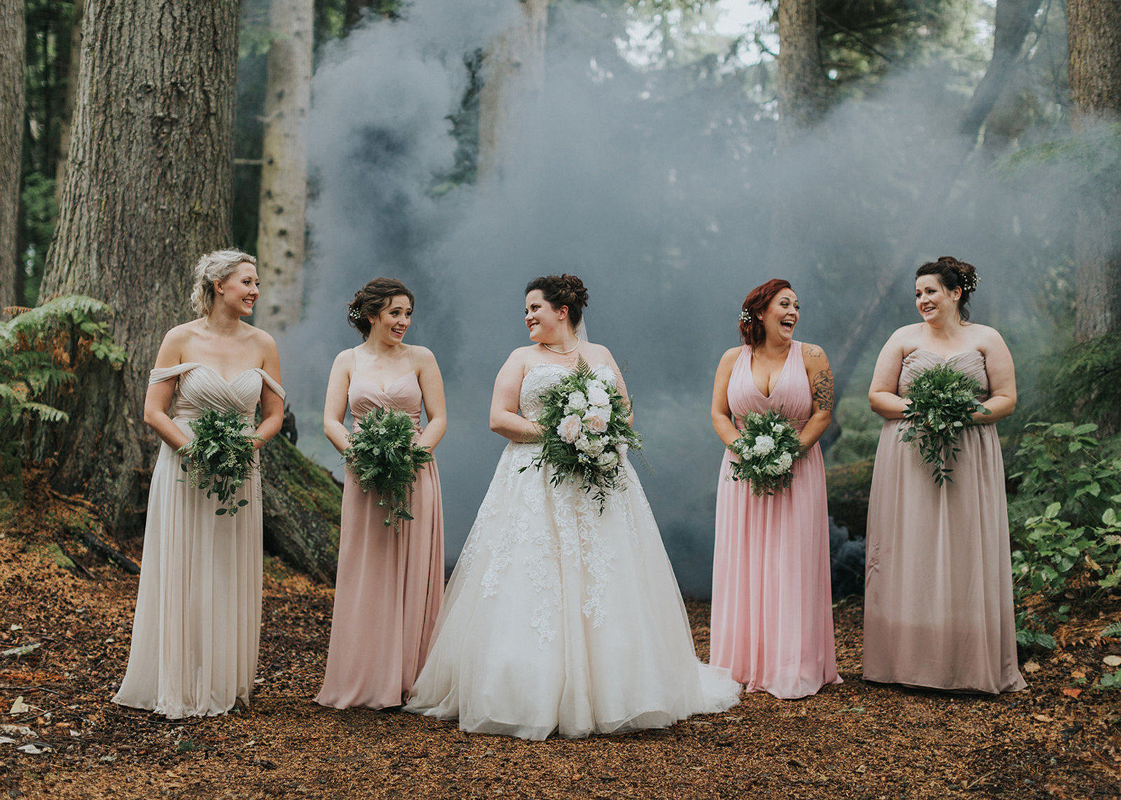 Bride and her bridesmaids sharing a laugh in the forest