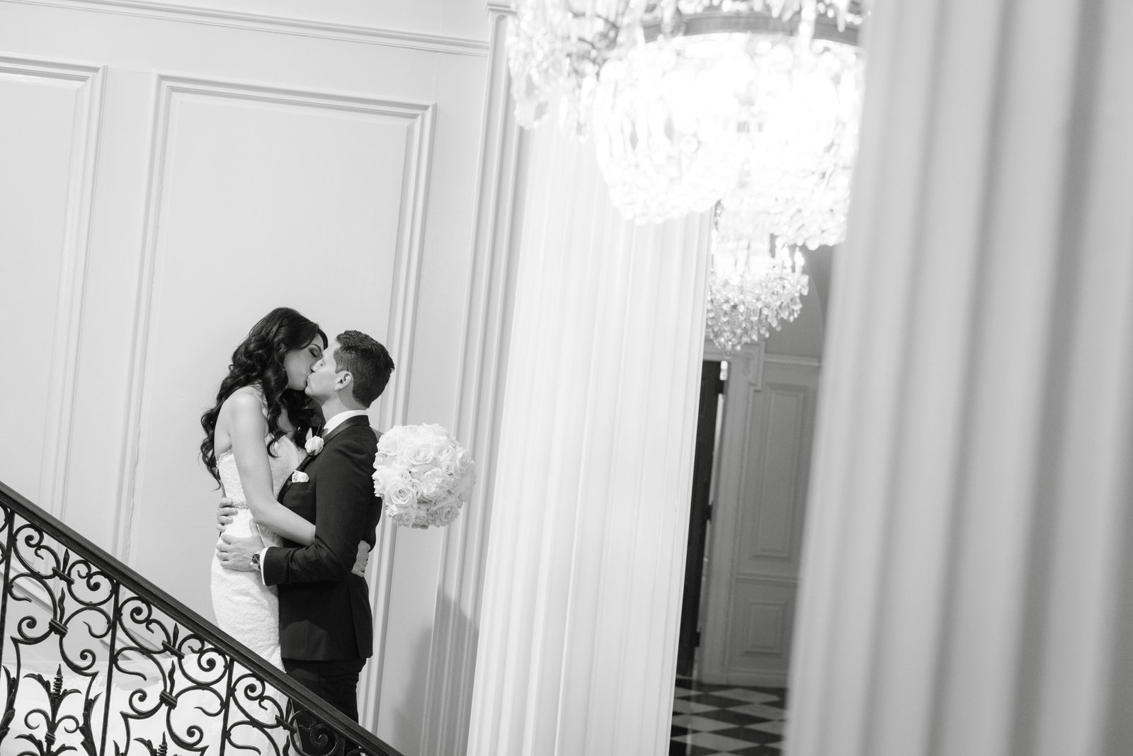 Bride and groom kissing at the stairs at Glen Cove Mansion