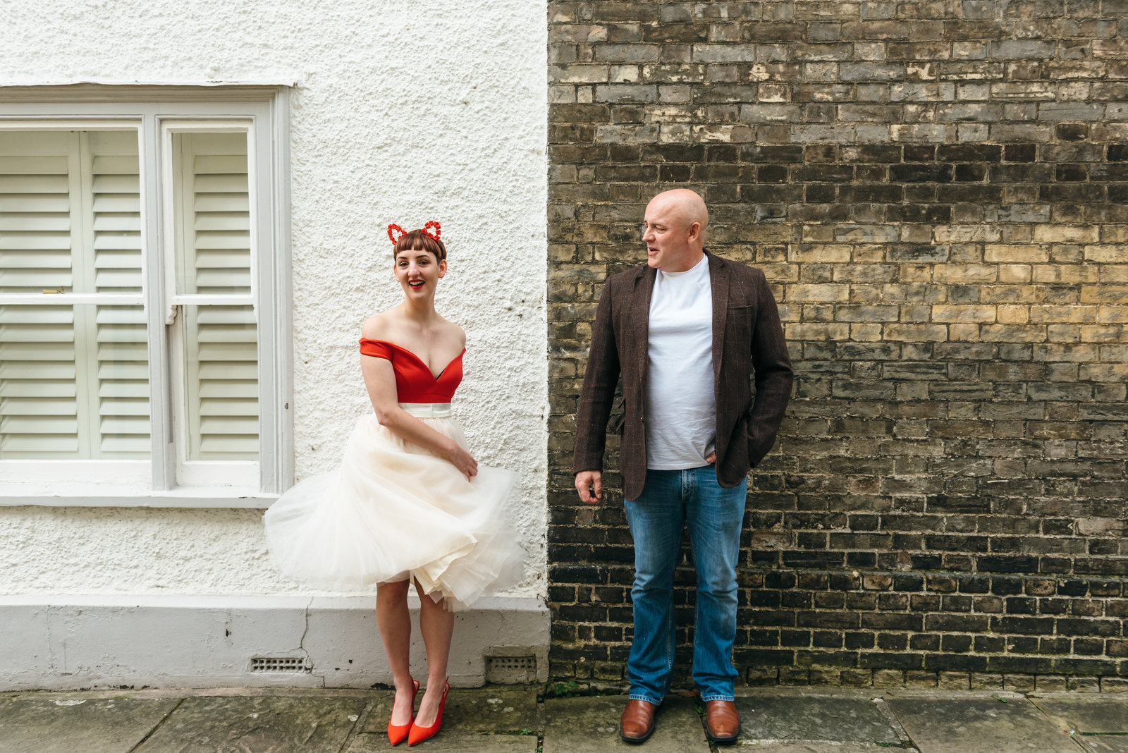 Lisa and Neil stand in front of a brick wall in Norwich. Lisa is twirling and holding her skirt and looking at the camera and Neil is looking at her and smiling.