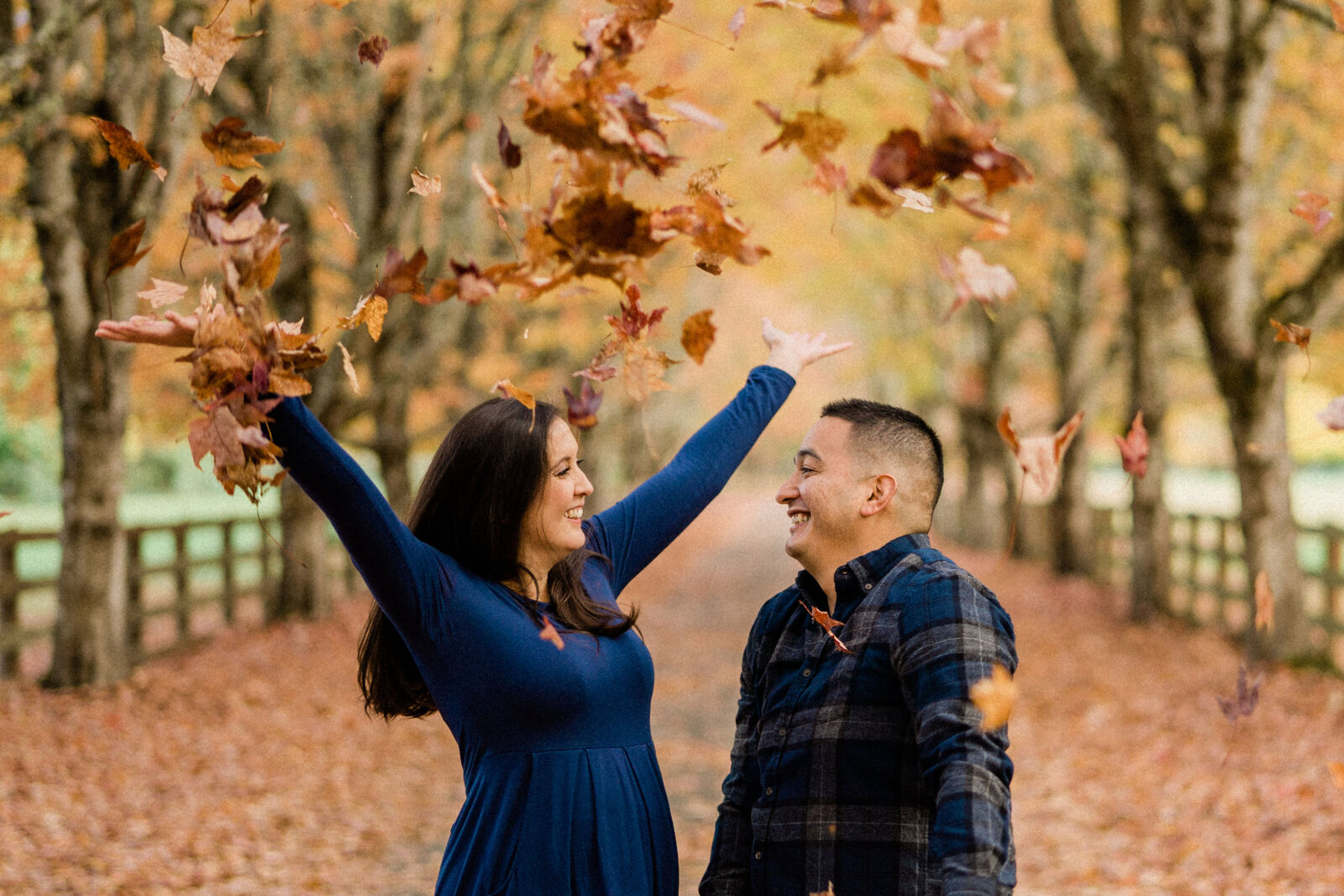 Bride and groom throwing fall leaves at Rockwood Farm, one of the best places for engagement photos in Seattle during autumn.