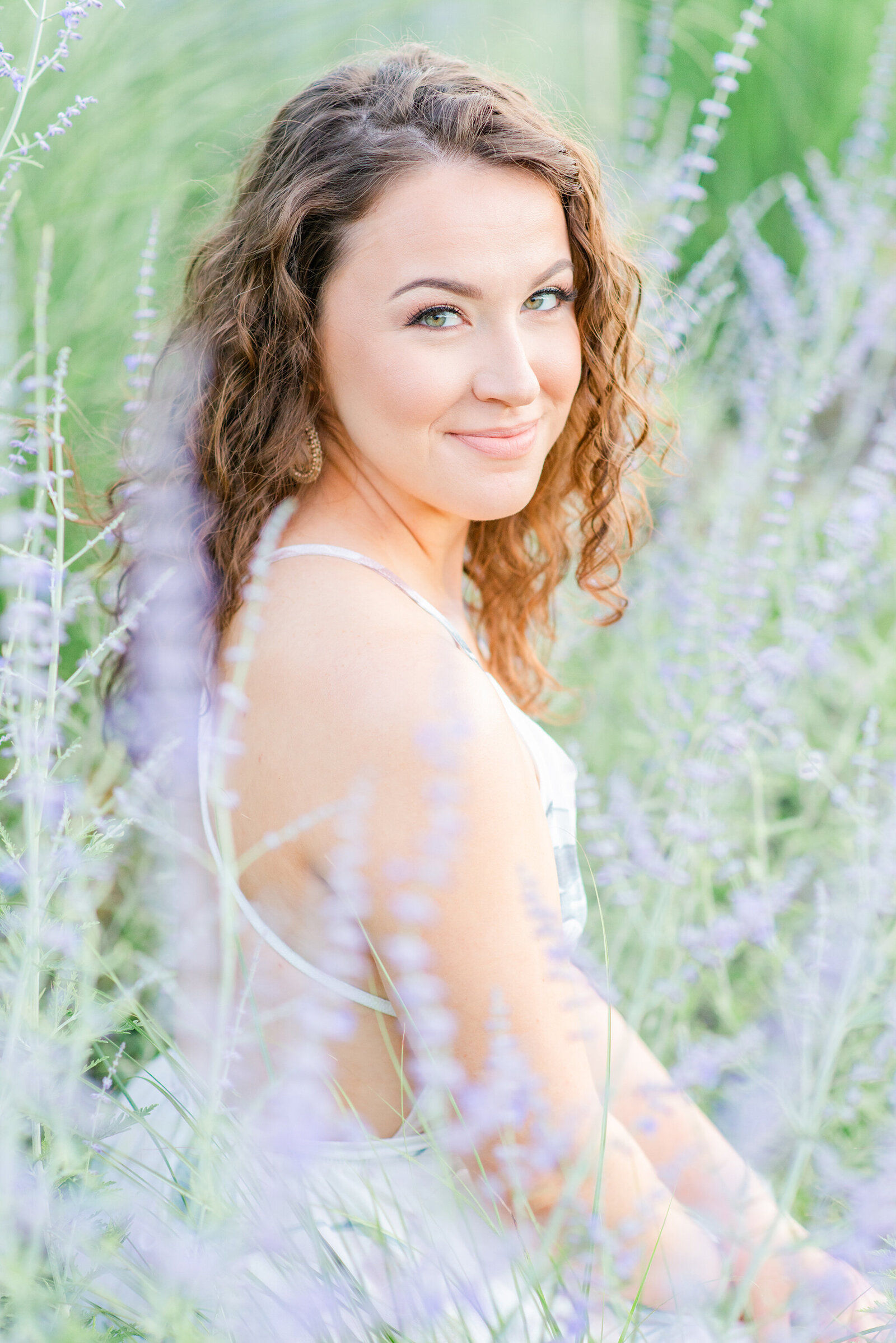 Woman looking at camera while sitting in a lavender field