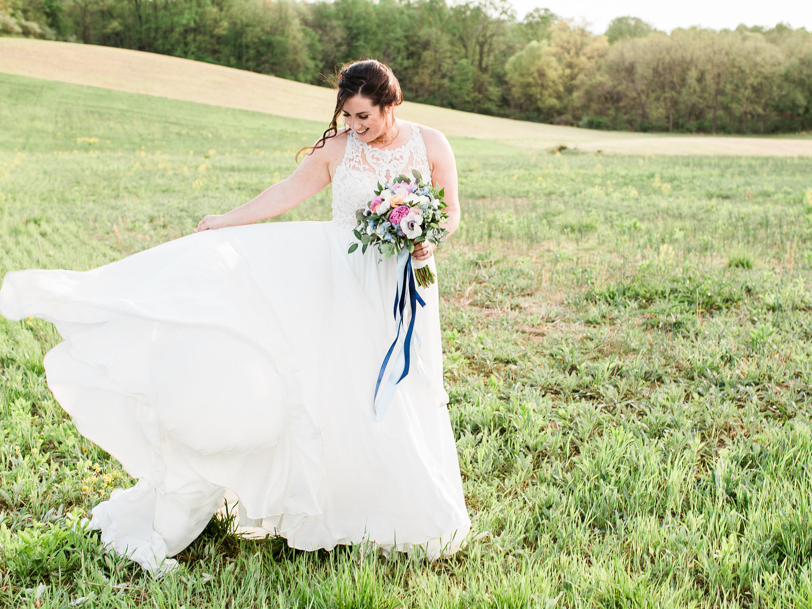Bride in flowing dress, with colorful bouquet lifts her dress so it blows in the wind while she stands in a big field in Maryland