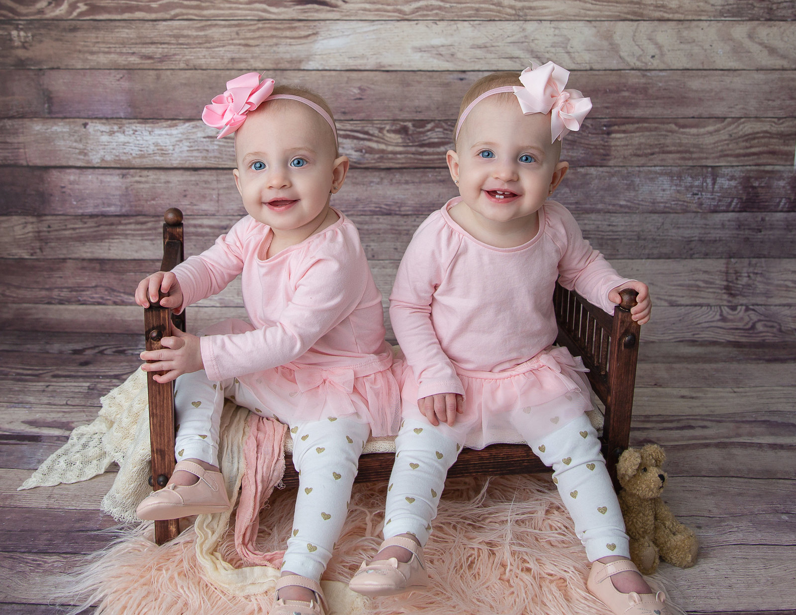Twin smiling girls sitting on a wood bed together, pink flokati underneath, pink shirts and pink headbands
