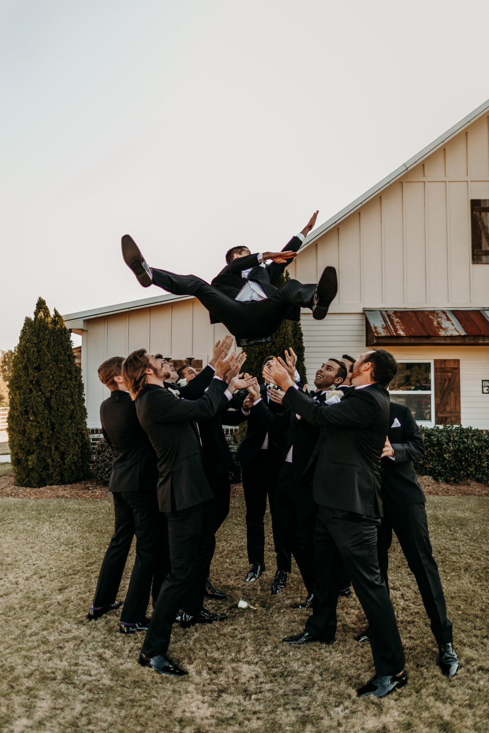 J.Michelle Photography photographs groomsmen through groom in the air at vintage oaks farm wedding in Athens, Ga