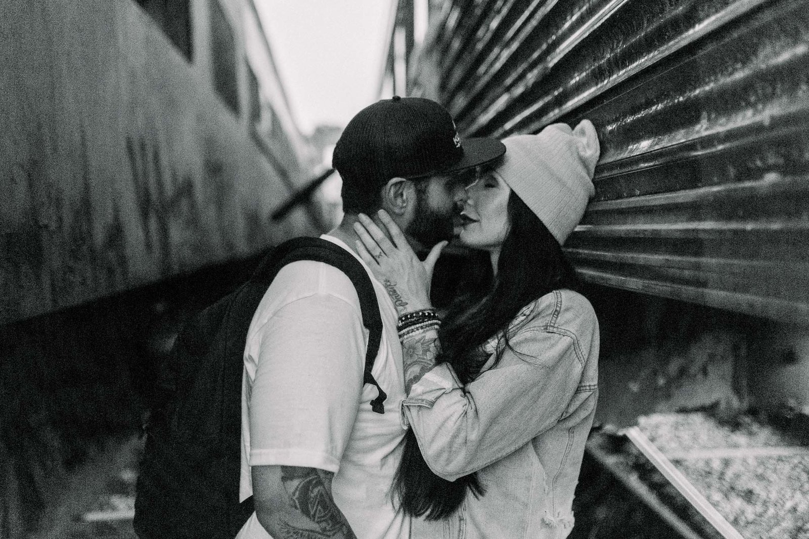 Couple kissing in between train cars captured by Staci Addison Photography