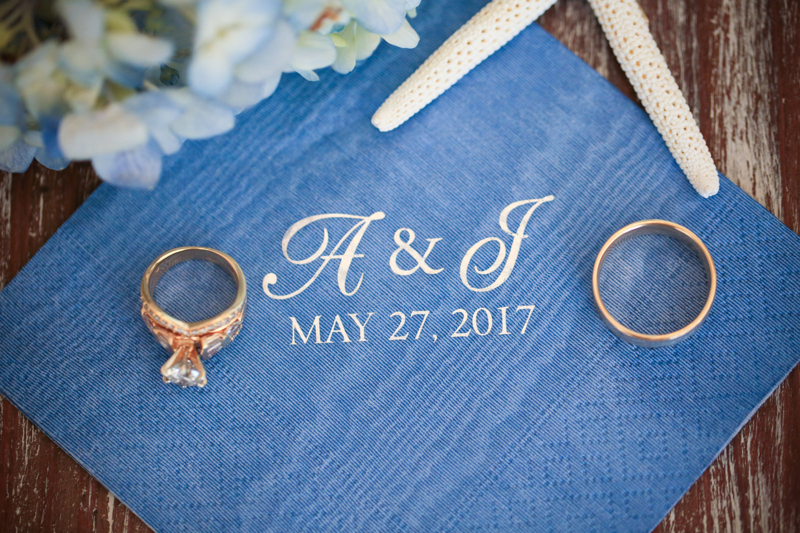 Anna Maria Island Wedding photography detail shot of the wedding rings with the  monogramed cocktail napkins