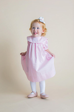 toddler girl in pink dress with her tongue