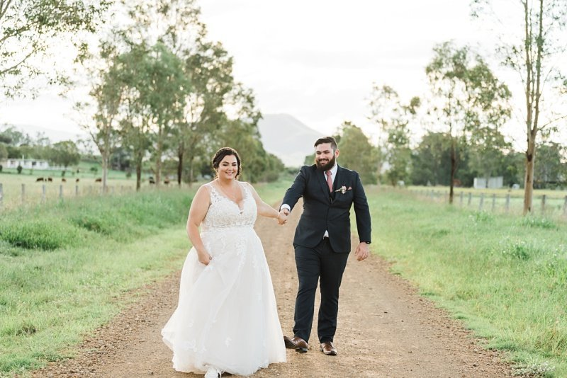 couple running along dirt road on their wedding day