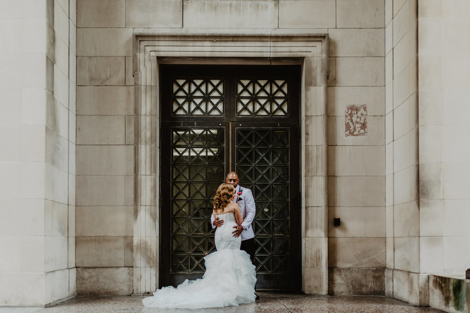 Bride and Groom stand in front of iron doors wrapped up at War Memorial