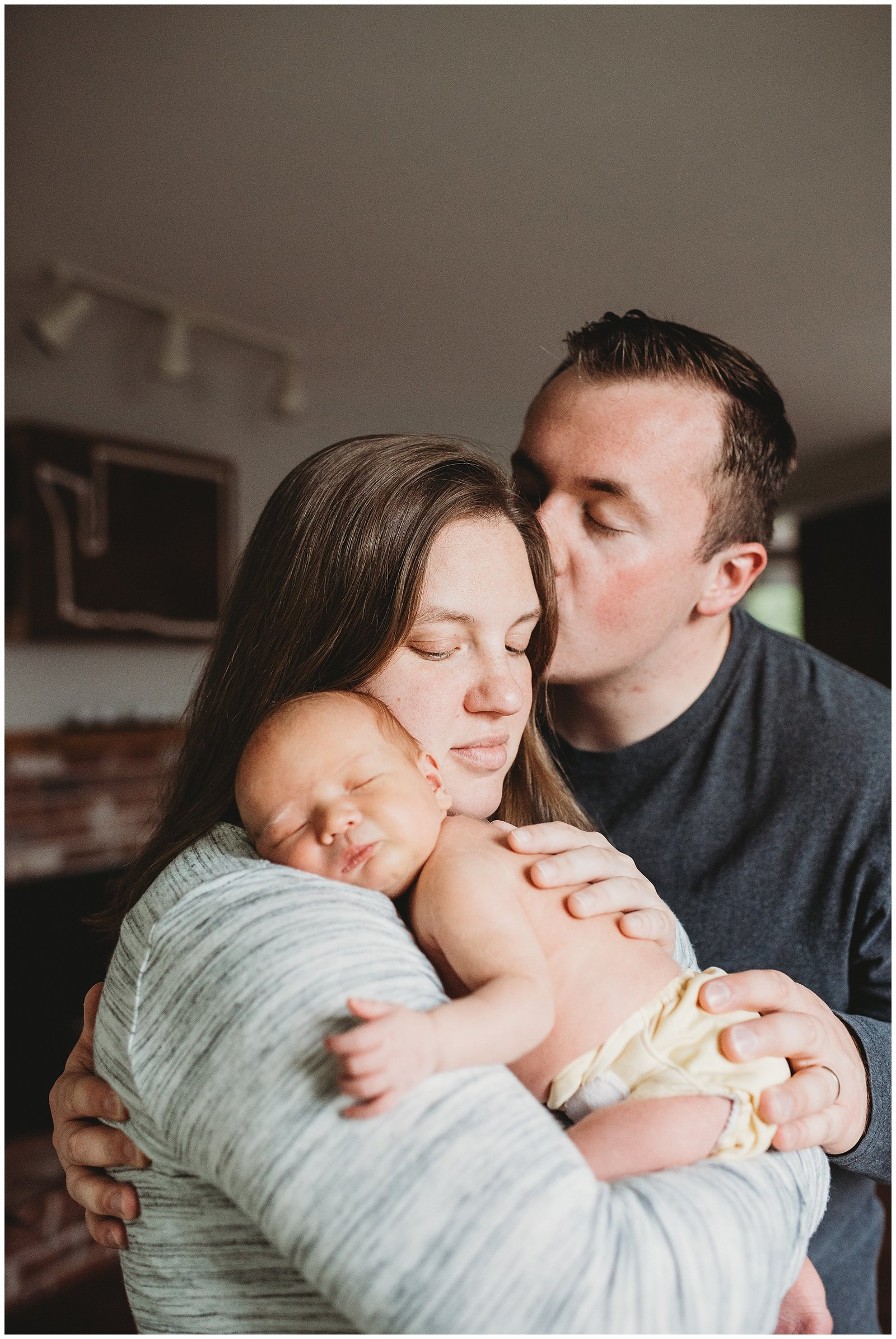 dad kissing mom holding newborn baby boy in home lifestyle photoshoot Emily Ann Photography Seattle Photographer