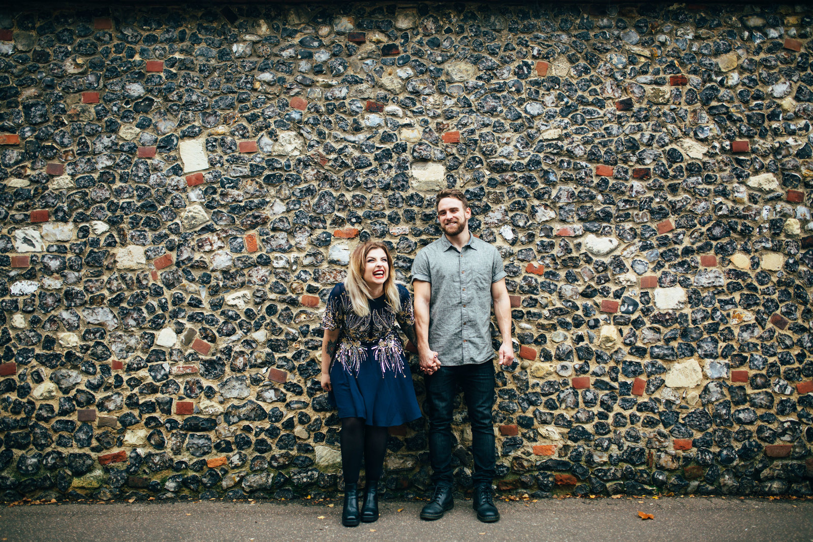Happy engaged couple Helen Anderson leans against grey brick wall for a natural couples photo