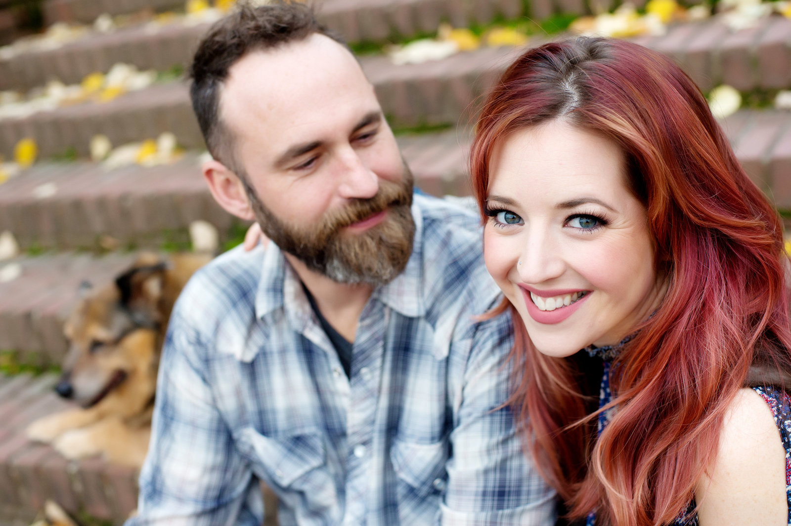 a girl with pretty red hair laughs at the camera as her fiance and dog sit next to her