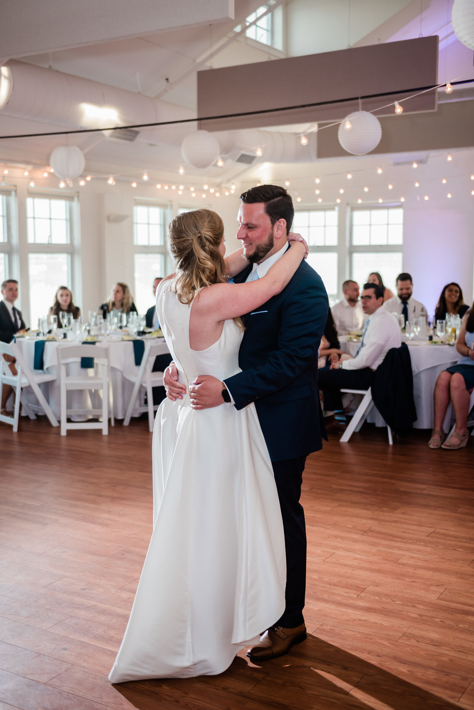 couple shares their first dance at their duxbury bay maritime school wedding reception