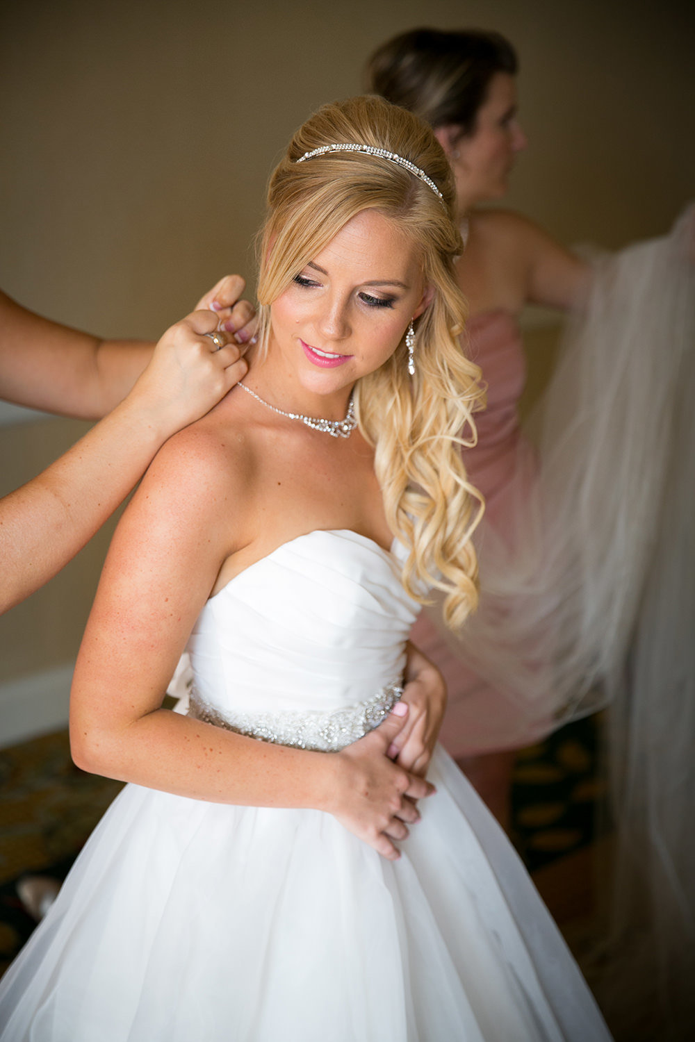 Beautiful blonde bride putting on the finishing touches for her wedding day