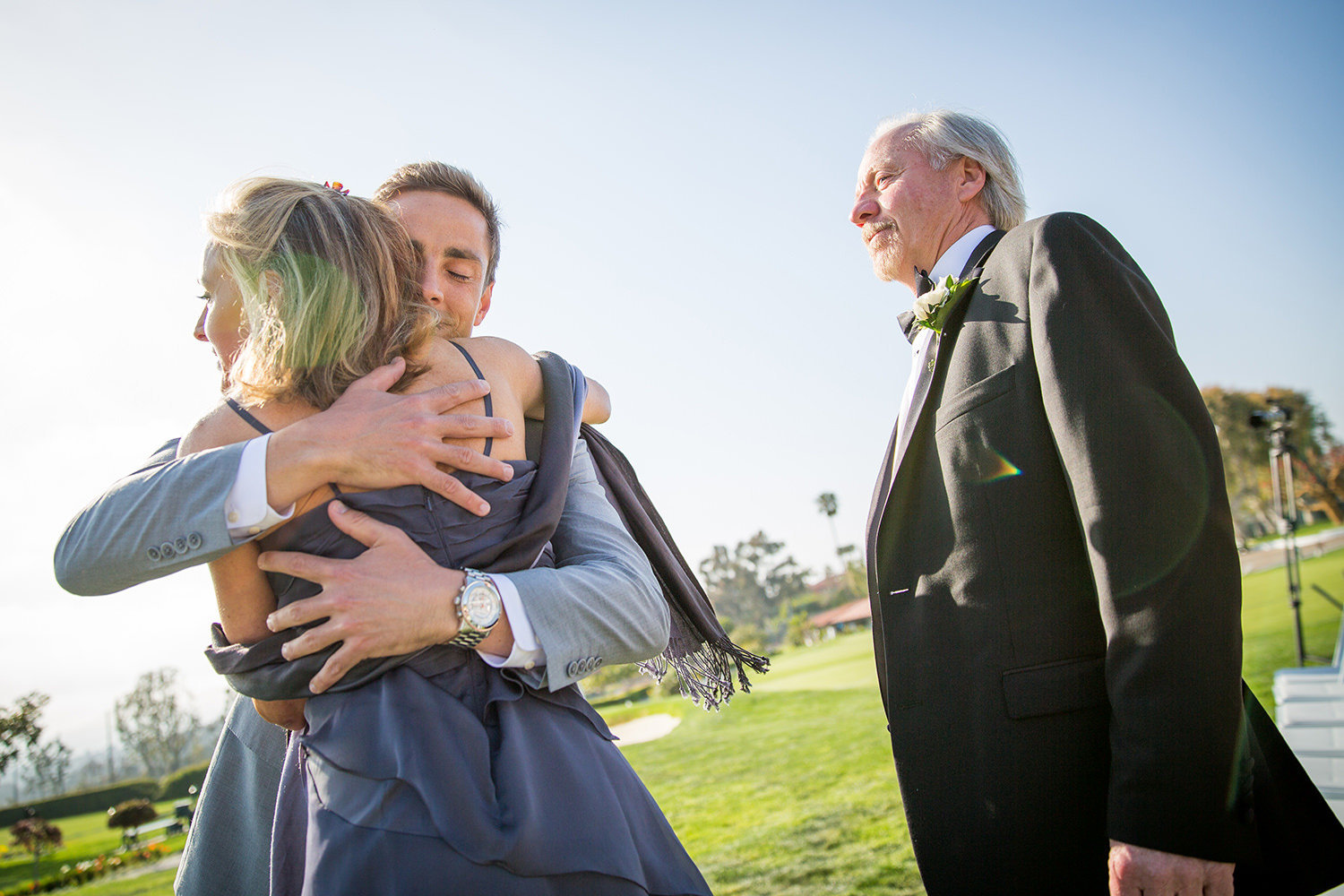 groom hugging parents at ceremony