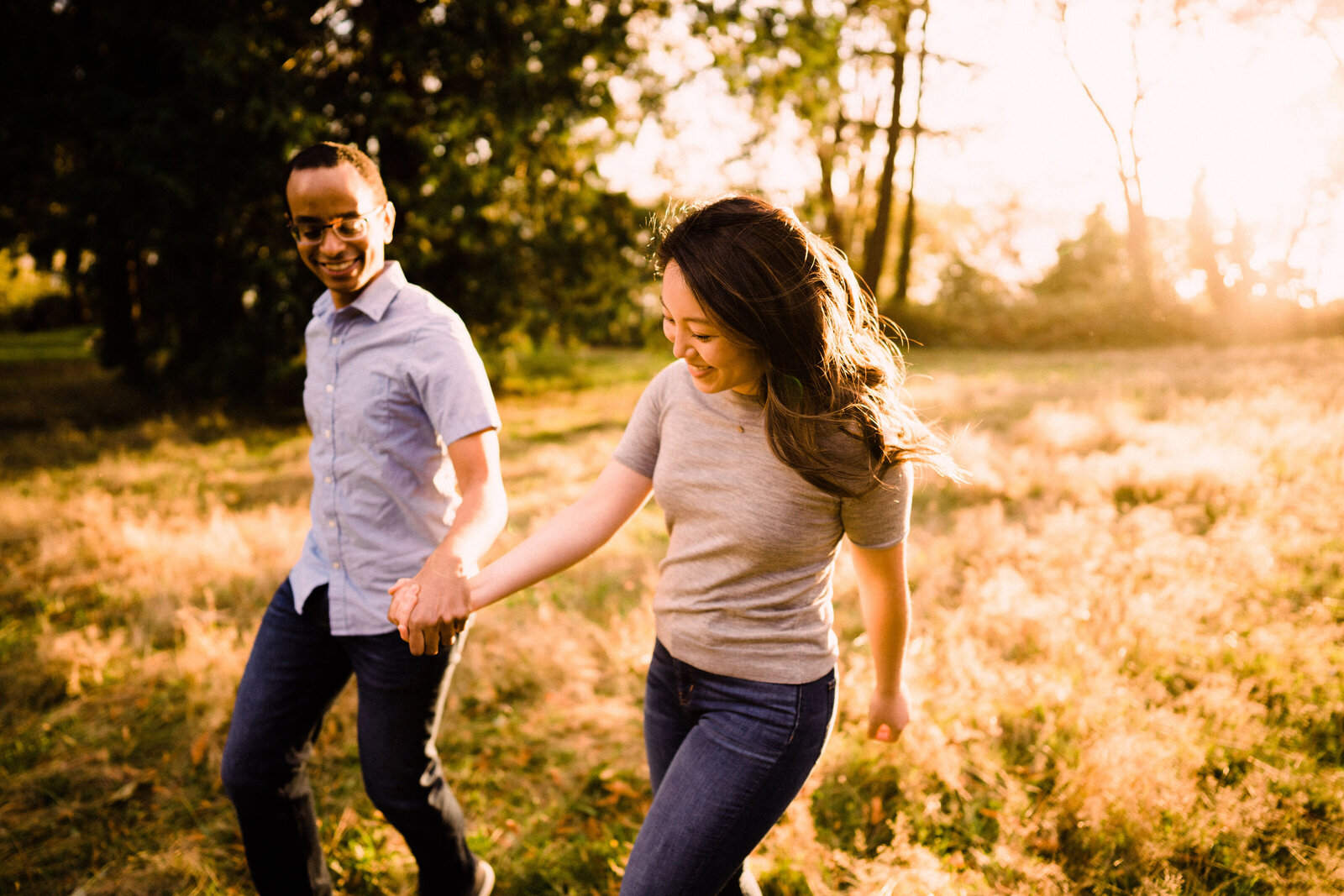 Engaged couple strolling through meadow at sunset at one of the best spots for engagement photos in Seattle, Lincoln Park, in West Seattle.