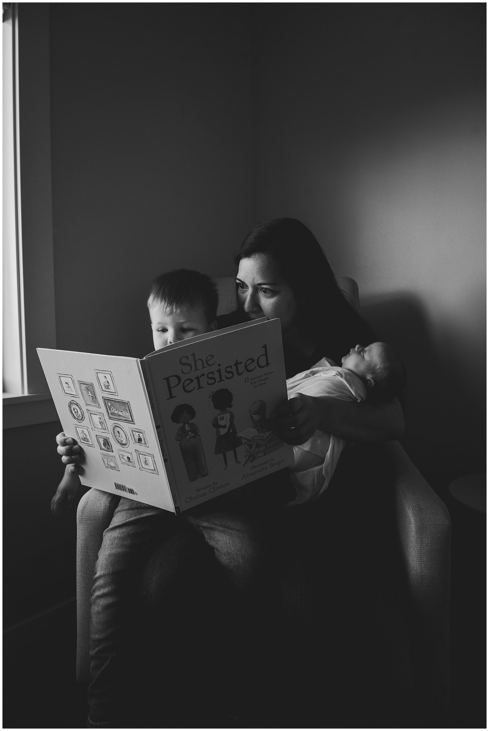 mom reading to newborn baby girl and big brother