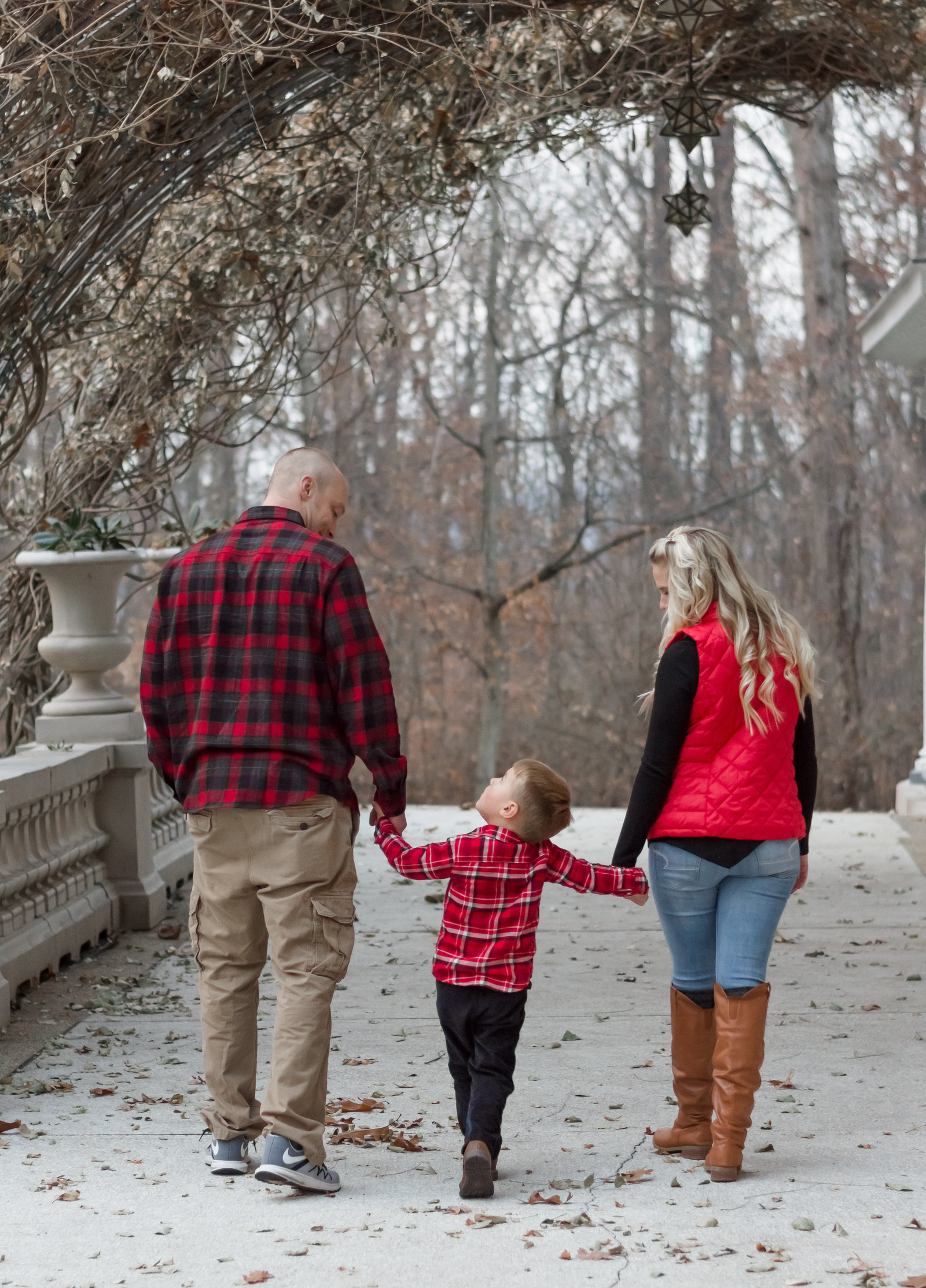 Family of three wearing red and plaid for holiday photos at the Liriodendron