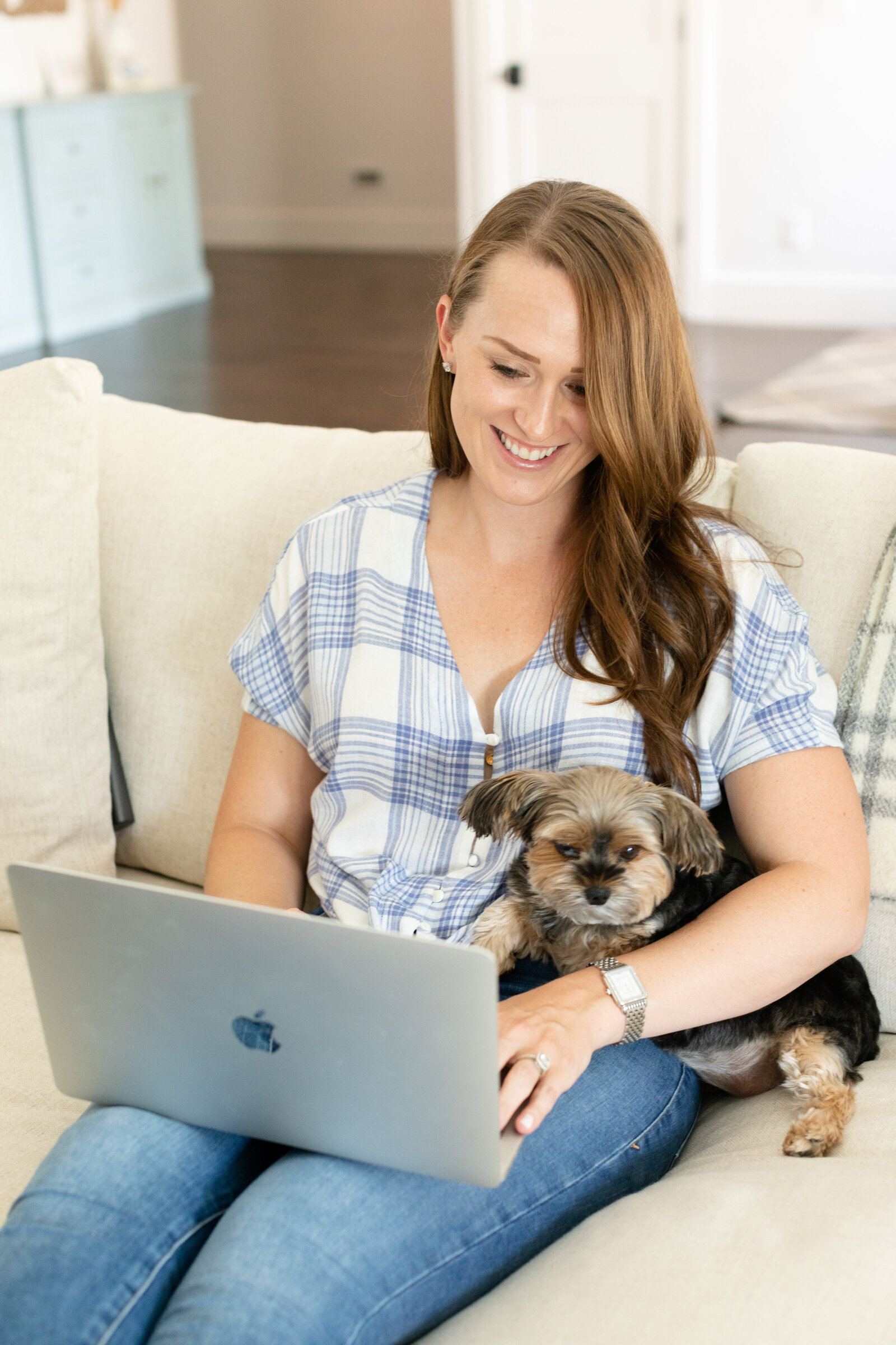 girl sitting on the sofa with her dog