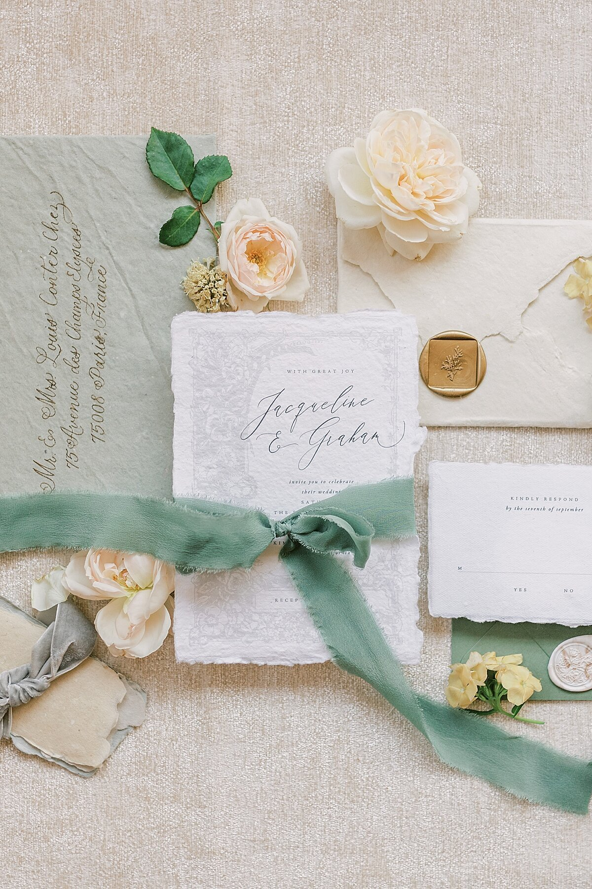 Wedding invitation flatlay with peach florals and green ribbon