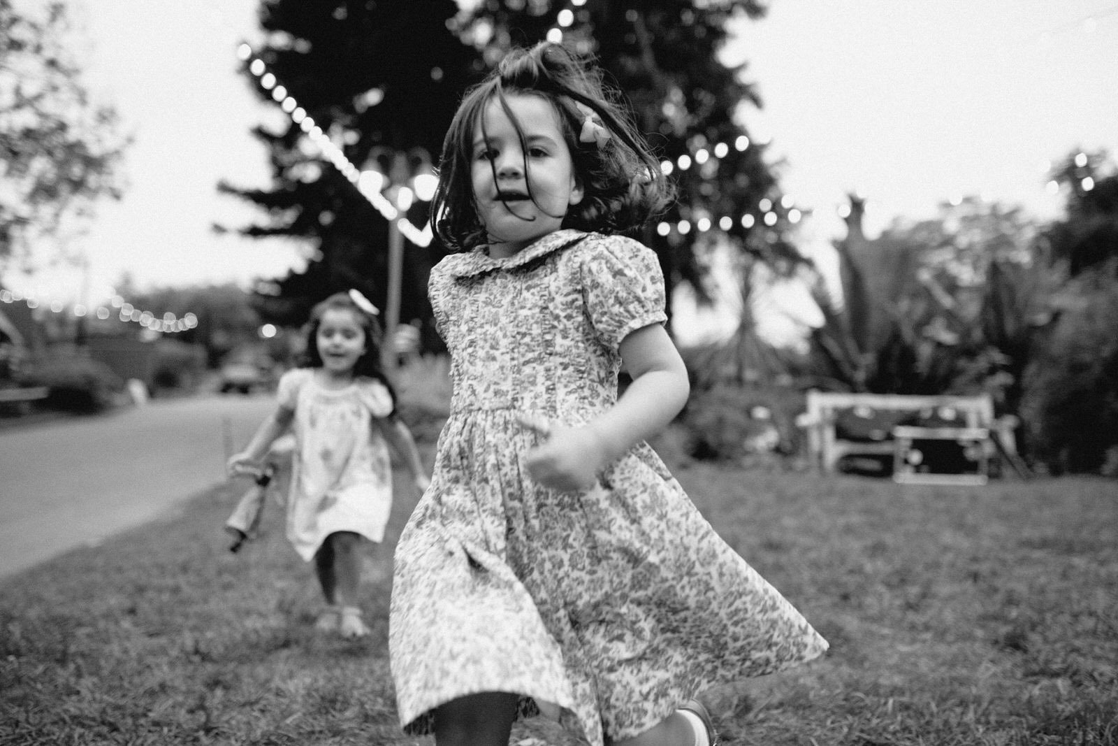 black and white image of two little girls in floral dresses running at the camera