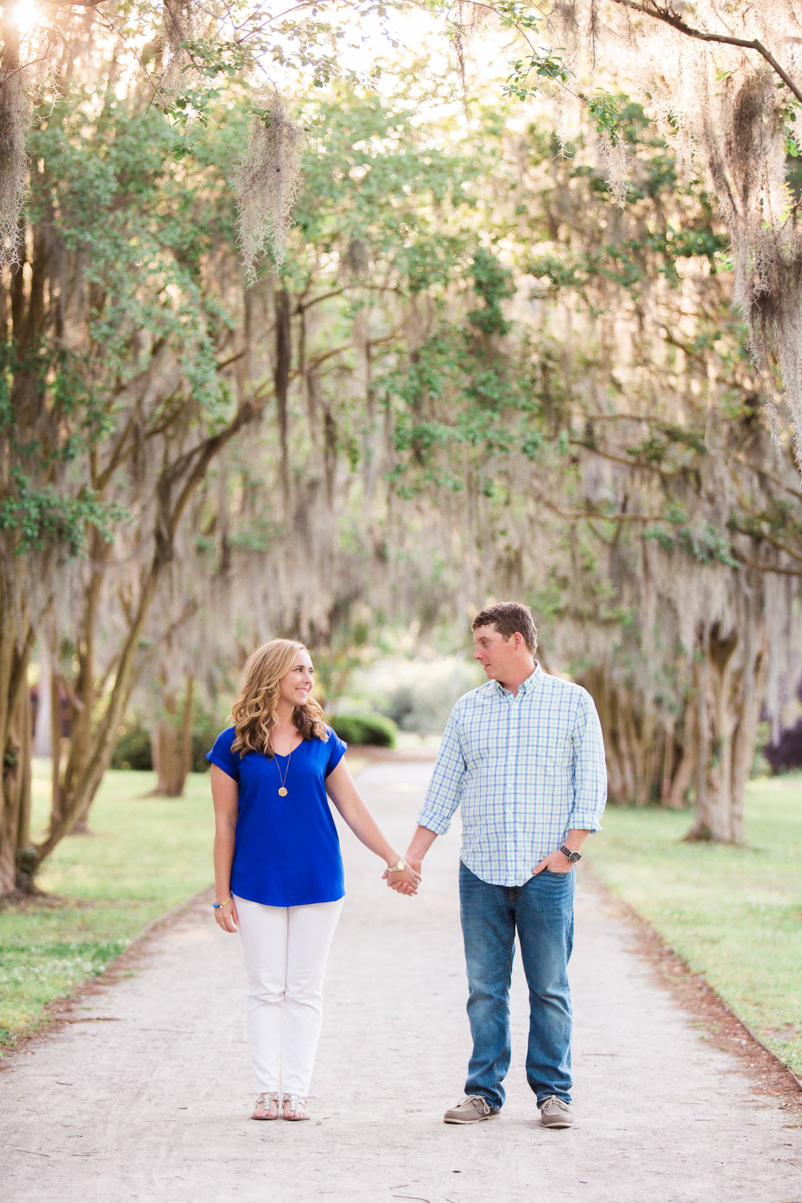 Engaged couple stand in pathway full of trees and spanish moss, Hampton Park, Charleston, South Carolina
