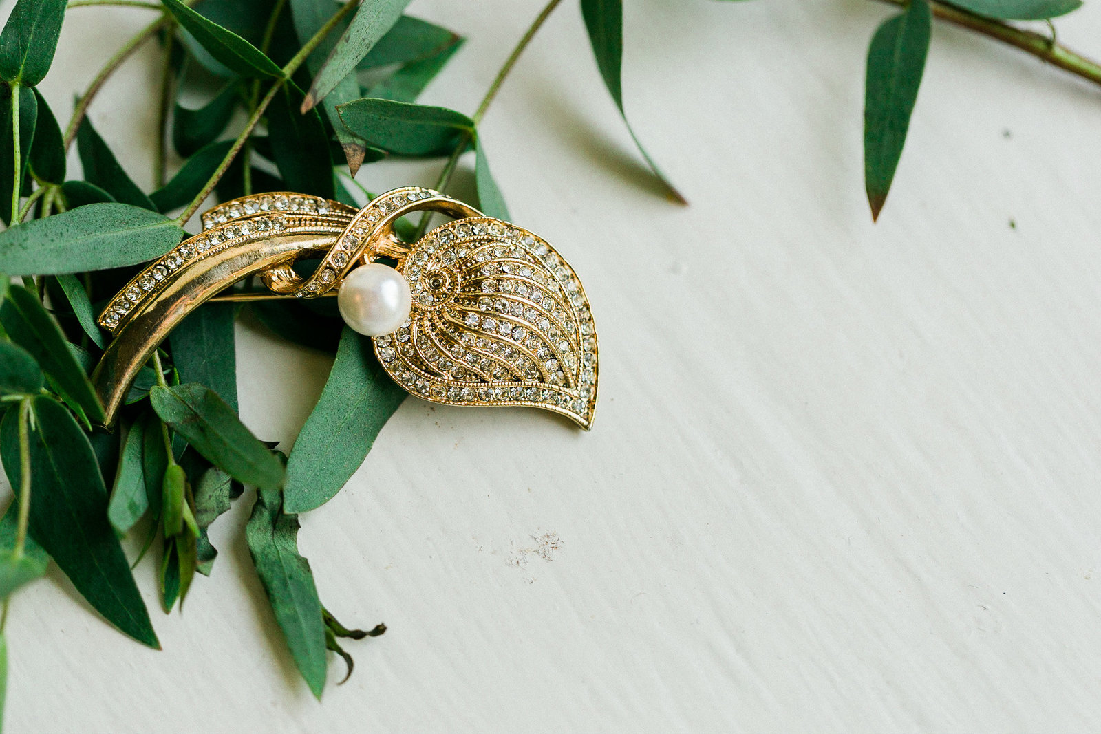 Heirloom broach on white wood with greenery