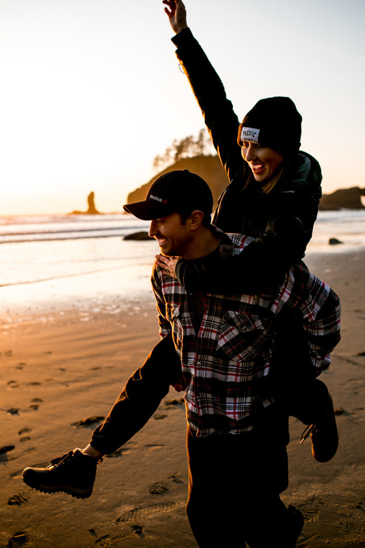 Engaged couple at LaPush Beach giving a piggy back ride.