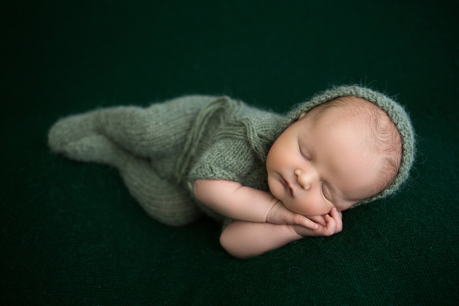 Posed in-studio portrait of newborn baby sleeping, green outfit and background