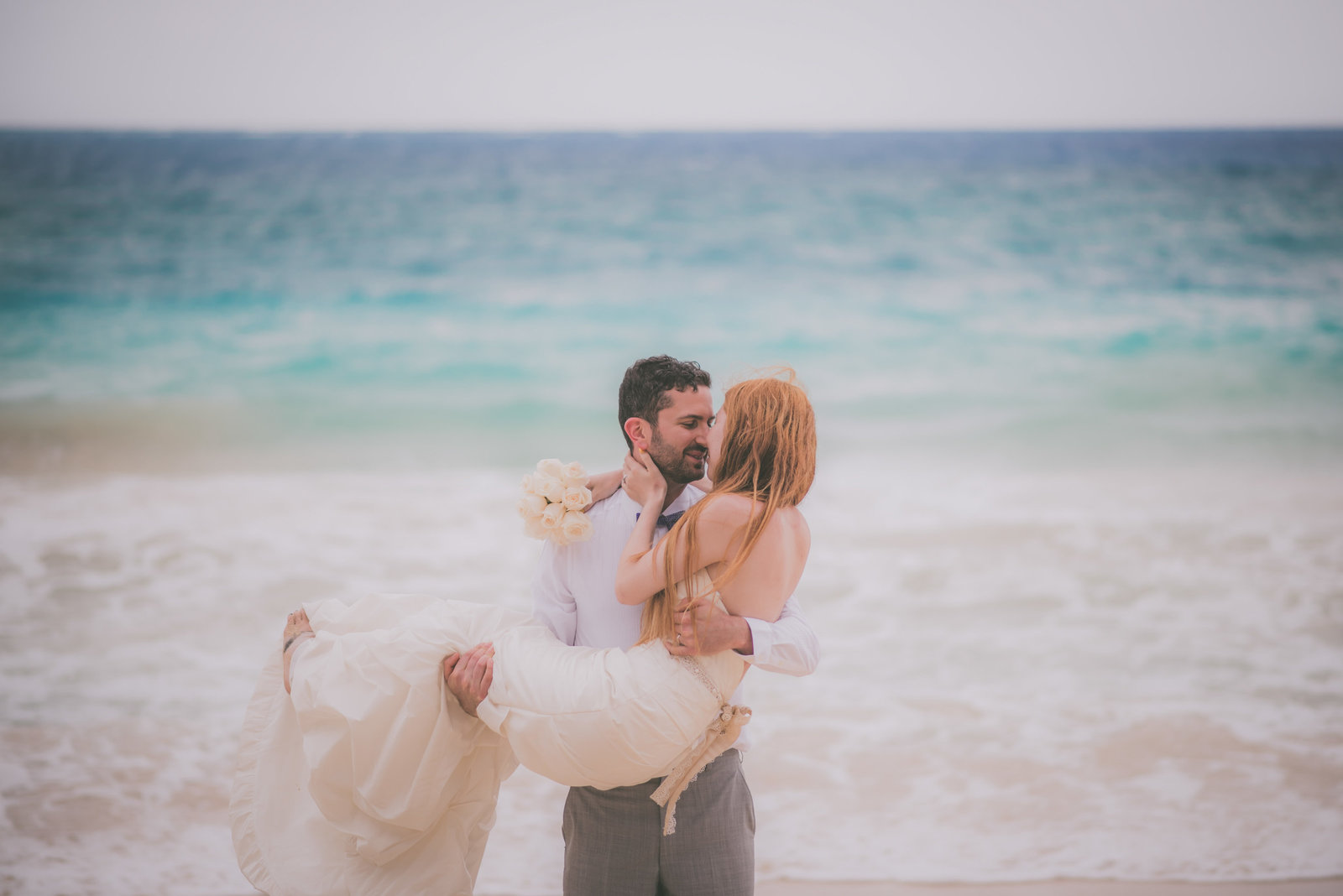 Groom holds bride on Hawaii beach while their faces get close.