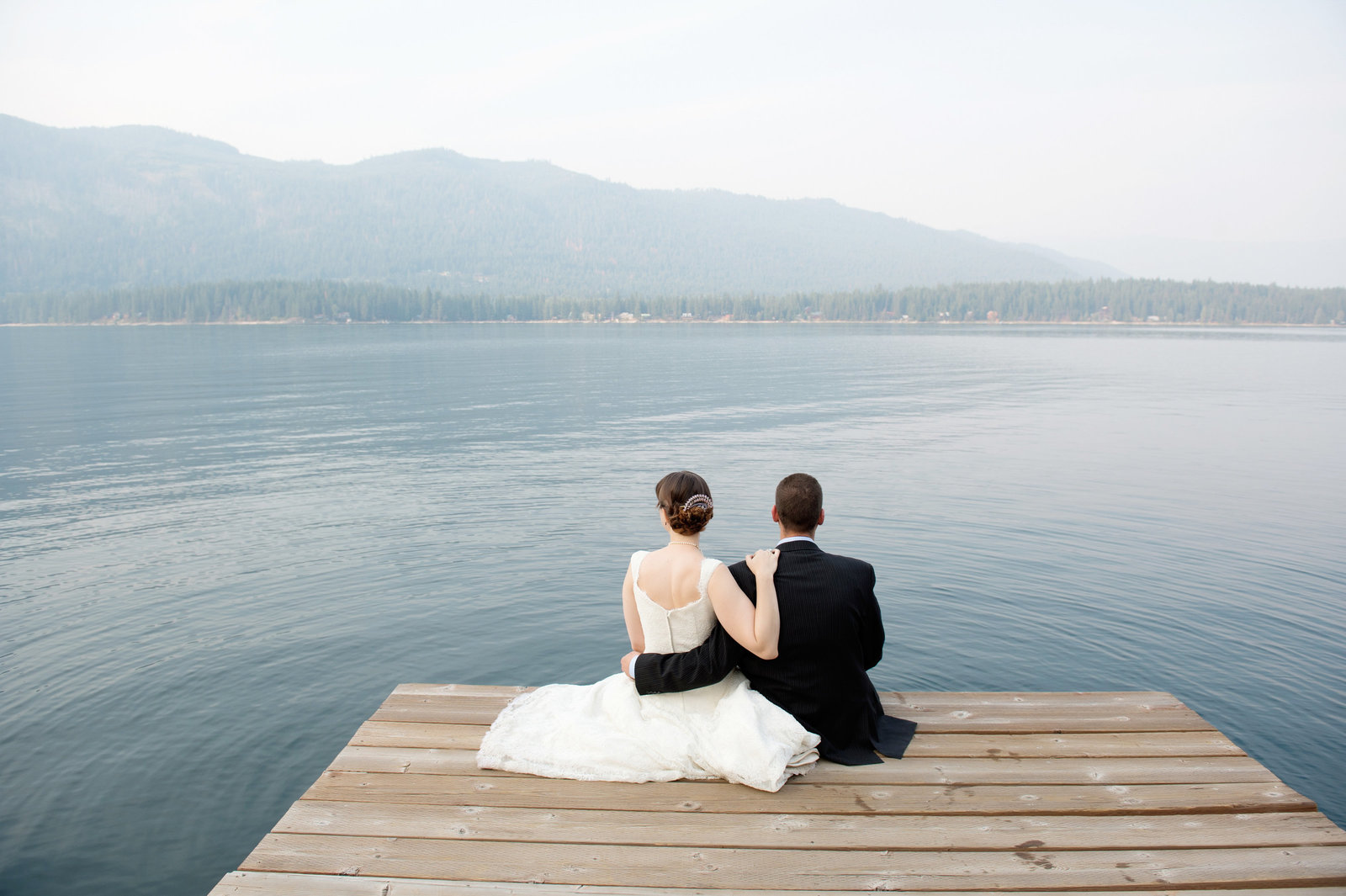 bride and groom sit on dock at camp zanika lache