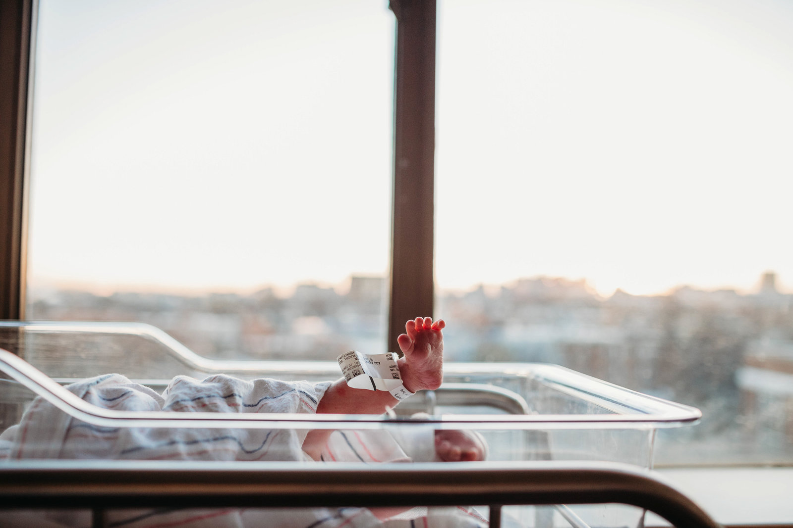 newborn sticks foot over the top of hospital bassinet during boston newborn photography session