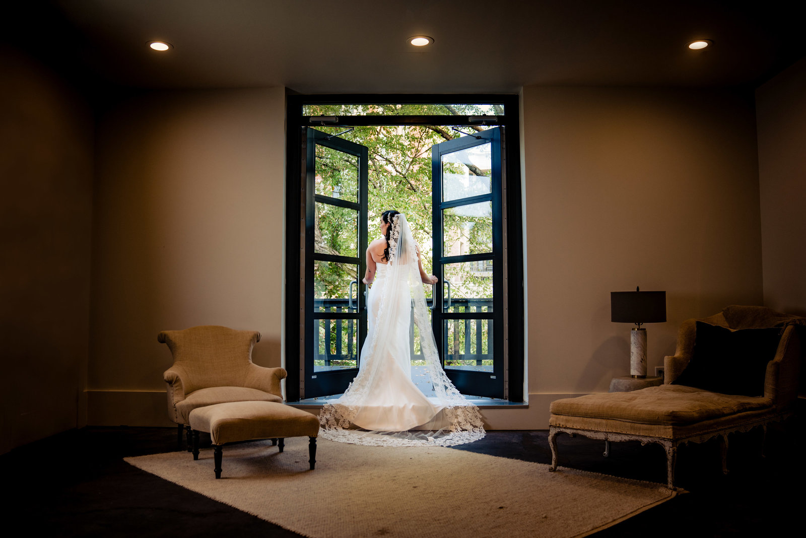 bride standing in front of glass doors
