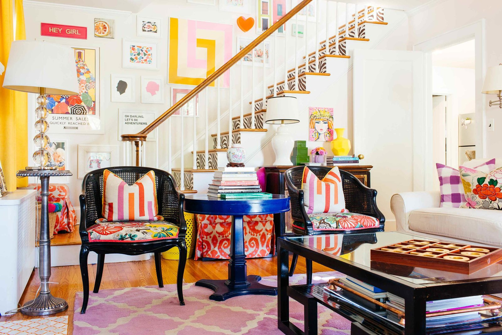A colorfully decorated living room with a staircase backdrop.