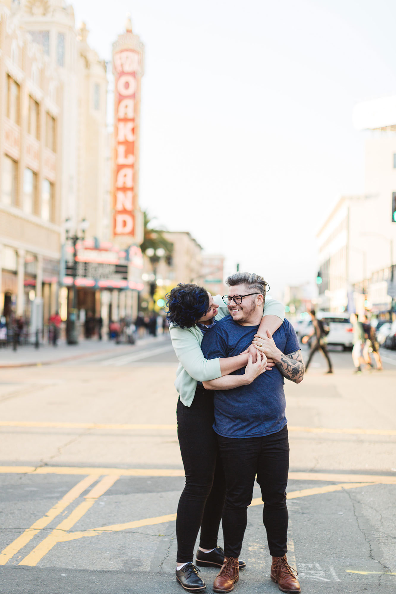 couple looking happy on their engagement shoot with fox theater oakland sign behind them